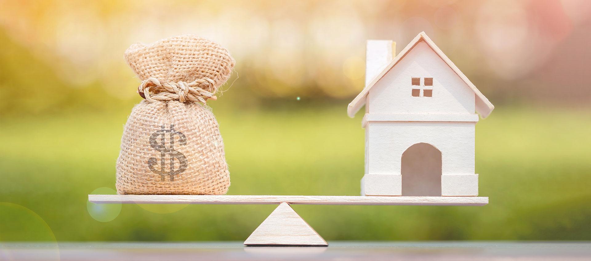 Abbildung Waage mit Geld und Haus