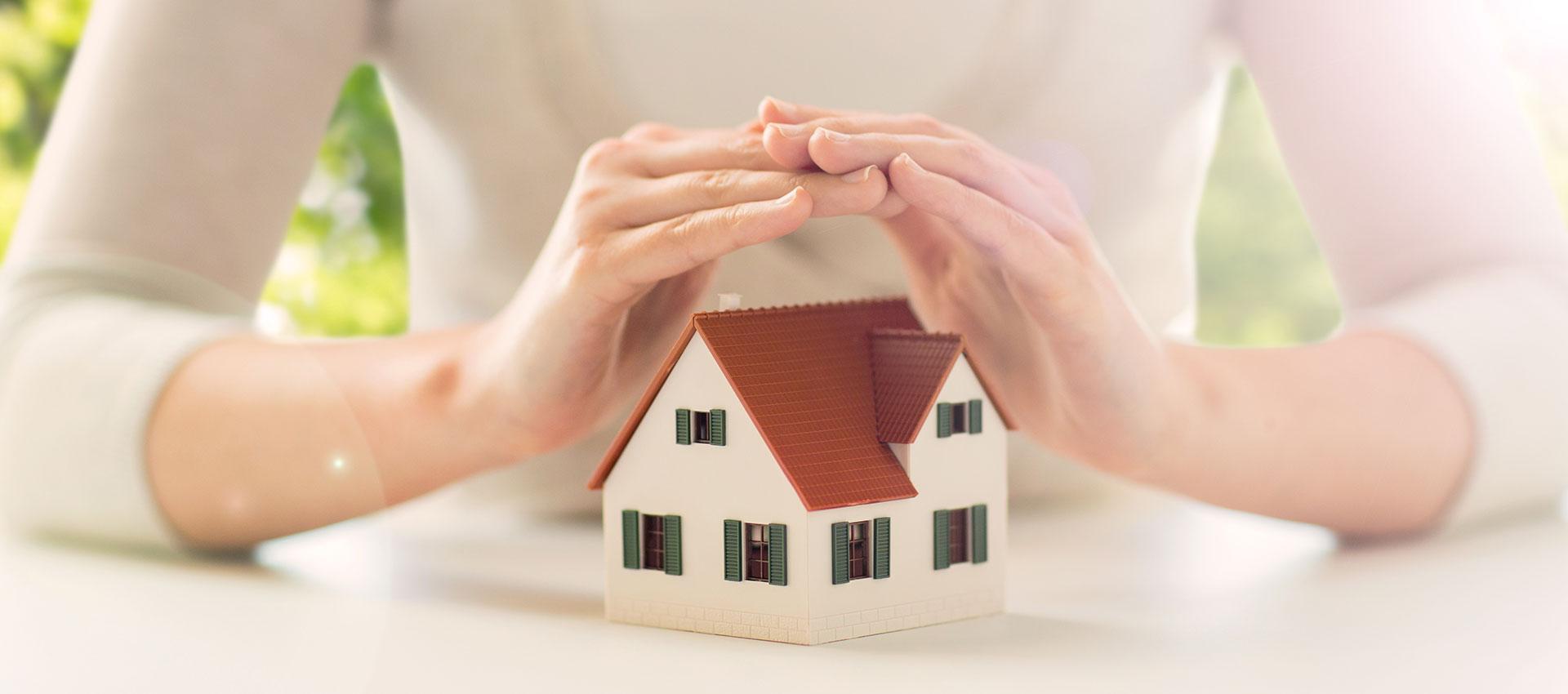 Abbildung Haus geschützt von zwei Händen